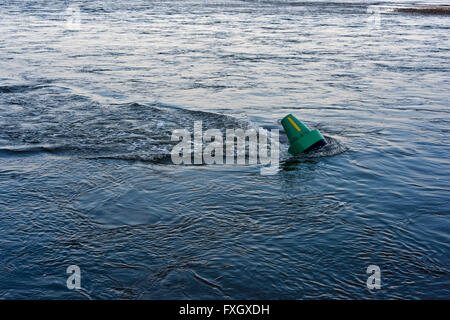 Green cardinal navigation mark being dragged by fast tide - Stock Photo
