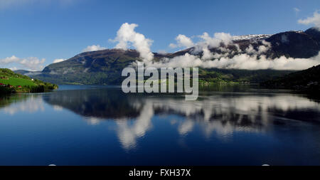 Early morning reflections in the Nordfjord at Olden. - Stock Photo