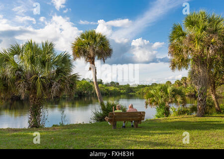 Couple sitting on bench overlooking water in Deer Prairie Creek in  Deer Prairie Creek Preserve in Venice Florida