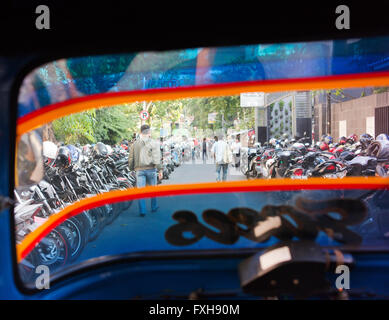 Many motorcycles parked in a Jakarta side street, as seen from a bemo. - Stock Photo