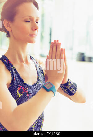 Serene woman practicing yoga with hands clasped - Stock Photo
