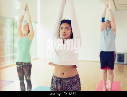 Woman with arms overhead in yoga class - Stock Photo