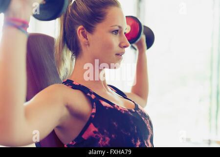 Focused woman doing dumbbell shoulder presses - Stock Photo
