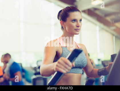Focused woman exercising on elliptical trainer in gym - Stock Photo