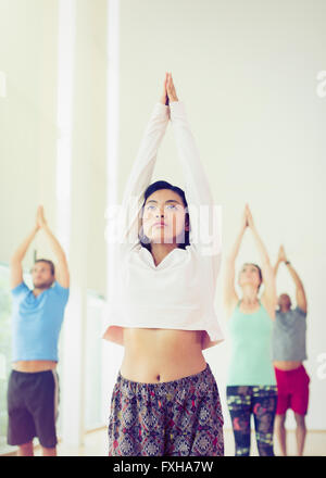 Serious woman with arms raised in yoga class - Stock Photo