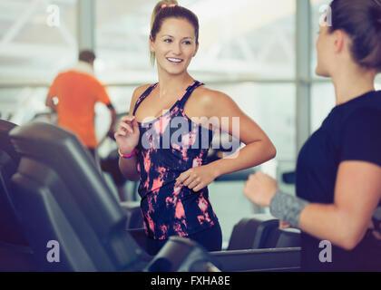 Smiling women talking on treadmills at gym - Stock Photo