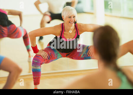 Smiling fitness instructor leading aerobics class - Stock Photo