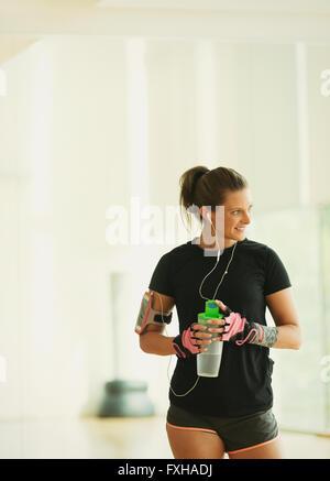 Smiling woman taking a break drinking water in gym studio - Stock Photo
