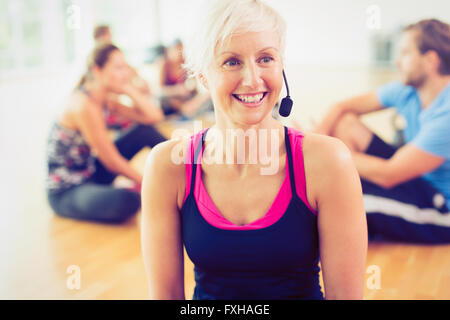 Smiling fitness instructor wearing headset - Stock Photo
