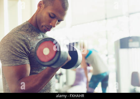 Focused man doing dumbbell biceps curls at gym - Stock Photo