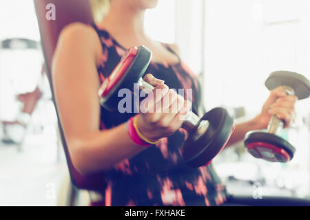 Blurred motion doing dumbbell biceps curls at gym - Stock Photo