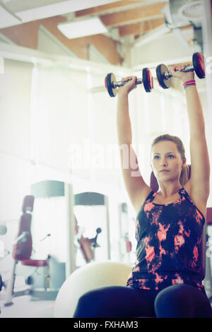 Focused woman doing dumbbell shoulder presses at gym - Stock Photo