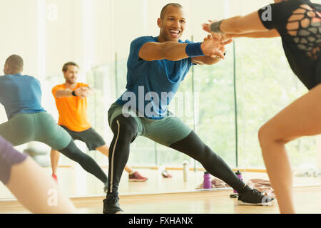 Enthusiastic fitness instructor leading aerobics class - Stock Photo