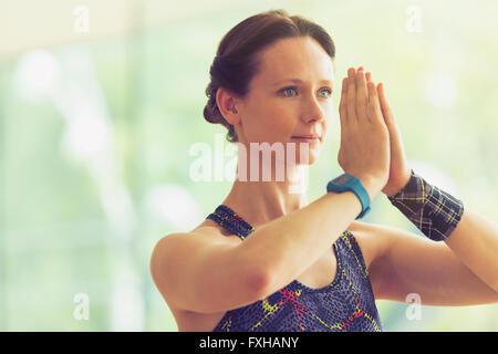 Calm woman with hands at prayer position in yoga class