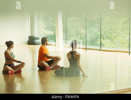 Man and women doing twisted stretch in gym studio - Stock Photo