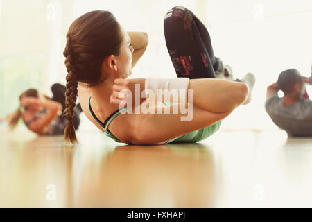 Woman doing bicycle sit-ups in exercise class - Stock Photo