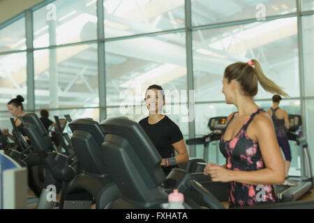 Smiling women talking and jogging on treadmills at gym - Stock Photo