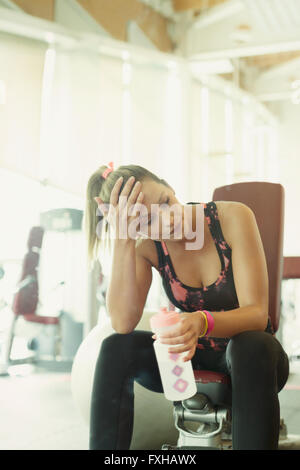 Tired woman resting and drinking water at gym - Stock Photo