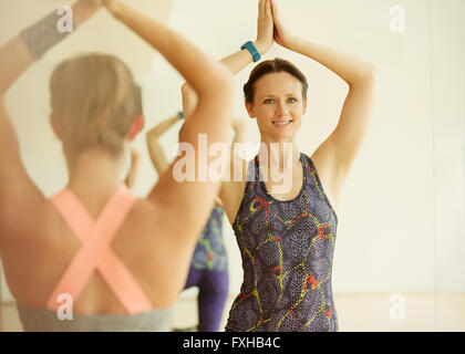 Portrait smiling woman with hands overhead in yoga class - Stock Photo