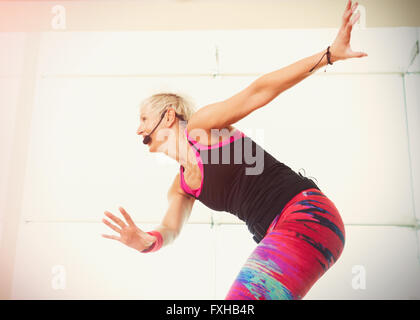 Energetic fitness instructor leading aerobics class with headset - Stock Photo