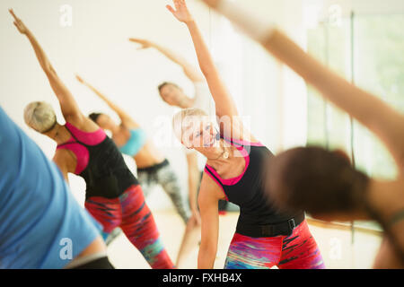 Smiling fitness instructor leading aerobics class stretching arms - Stock Photo