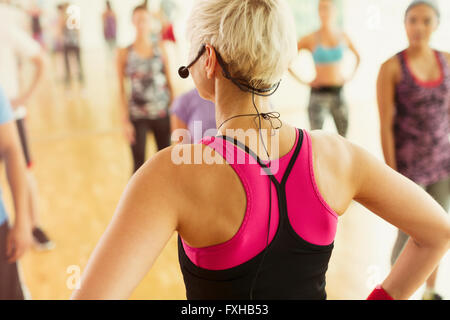 Rear view fitness instructor with headset leading aerobics class - Stock Photo