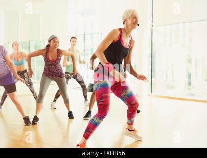 Energetic fitness instructor leading aerobics class - Stock Photo