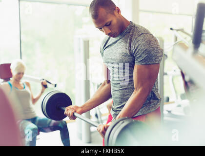 Focused man doing barbell biceps curls at gym - Stock Photo