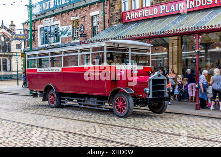 An old style coach or charabanc used giving tourists a sightseeing tour around coastal or urban areas of interest - Stock Photo
