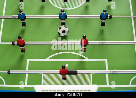 First person perspective view downward on one half of foosball set with little soccer ball - Stock Photo