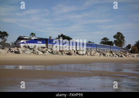 Amtrak Surfliner railroad locomotive on tracks along Pacific Ocean coast near Carpinteria in Southern California,United - Stock Photo