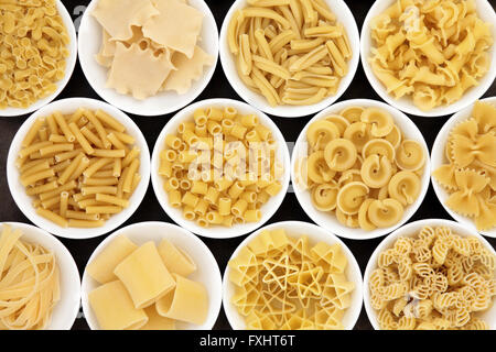 Pasta dried food selection close up in white porcelain bowls - Stock Photo