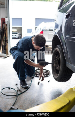 Mechanic changing car wheel with pneumatic wrench - Stock Photo