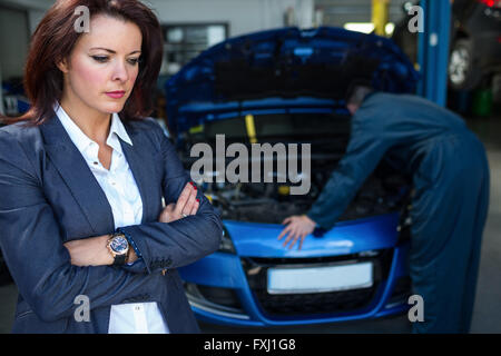 Customer with arms crossed while mechanic examining car - Stock Photo