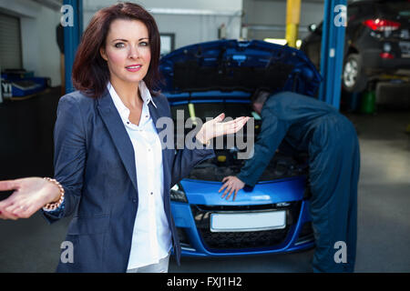 Worried customer with mechanic examining car - Stock Photo