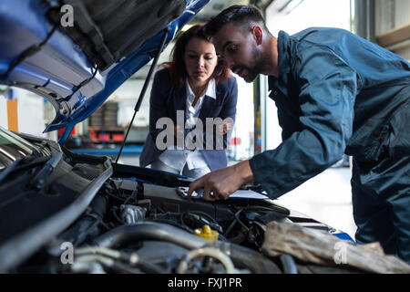 Mechanic showing customer the problem with car - Stock Photo