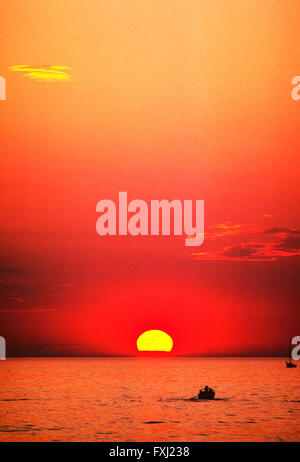 Orange sunset view of motor boat on Lake Michigan; Michigan; USA - Stock Photo