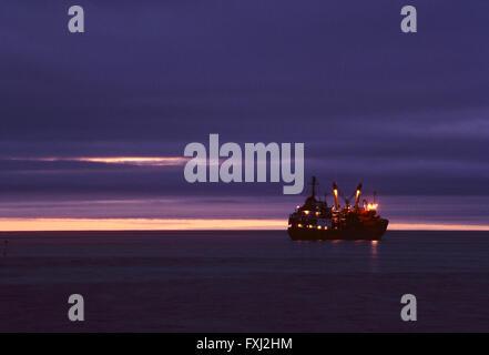 Dusk view; annual supply ship; Pangnirtung; Baffin Island; Nunavut; Canada - Stock Photo