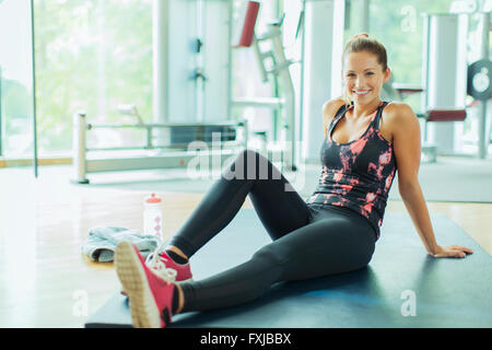 Portrait smiling woman resting on mat in gym - Stock Photo