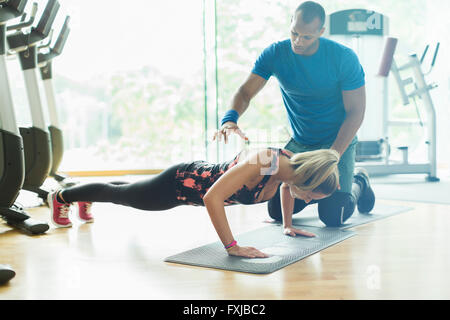 Personal trainer guiding woman doing push-ups at gym - Stock Photo