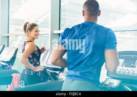 Man and woman jogging on treadmills at gym - Stock Photo