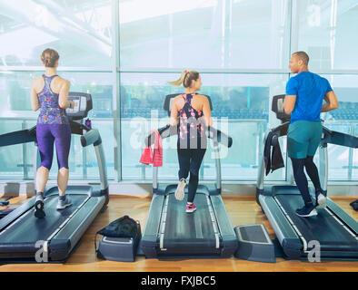 Man and women running on treadmills at gym - Stock Photo
