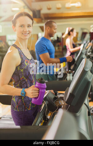 Portrait smiling woman with water bottle on treadmill at gym - Stock Photo