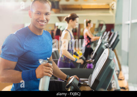 Portrait smiling man with water bottle on treadmill at gym - Stock Photo