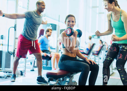 Woman cheering on friend doing dumbbell biceps curls at gym - Stock Photo
