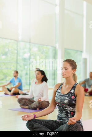Serene woman in lotus position with eyes closed in yoga class - Stock Photo