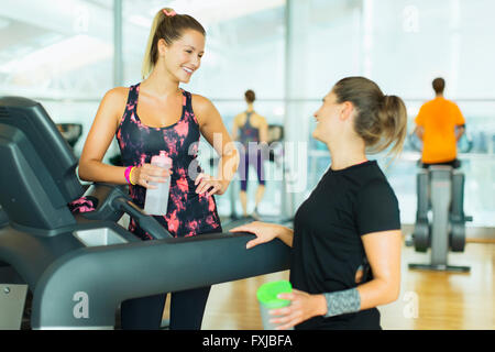 Smiling women resting and talking at treadmill in gym - Stock Photo