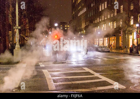 Steam rising from a sidewalk crossing on Newbury Street during a snow storm , Boston , MA , USA - Stock Photo