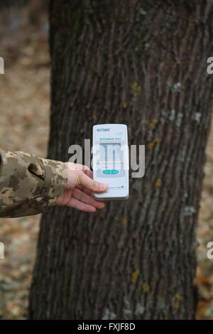 Measuring radiation levels with a Geiger counter in the Chernobyl exclusion zone, Ukraine - Stock Photo