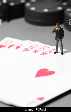 Miniature businessman poker hand chips gambling - Stock Photo